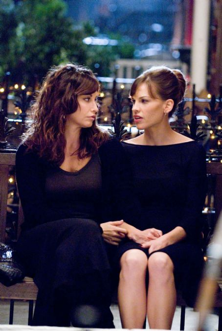 "P.S. I Love You GINA GERSHON as Sharon and HILARY SWANK as Holly Kennedy in Alcon Entertainment's romantic comedy "","" distributed by Warner Bros. Pictures. The film also stars Gerard Butler. Photo by Phil Caruso. TM & © 2007 Warner Bros."