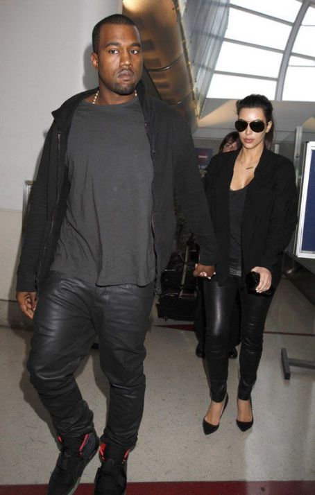 Kim Kardashian and Kanye West holding hands as they walk through LAX airport in Los Angeles, CA (July 16)