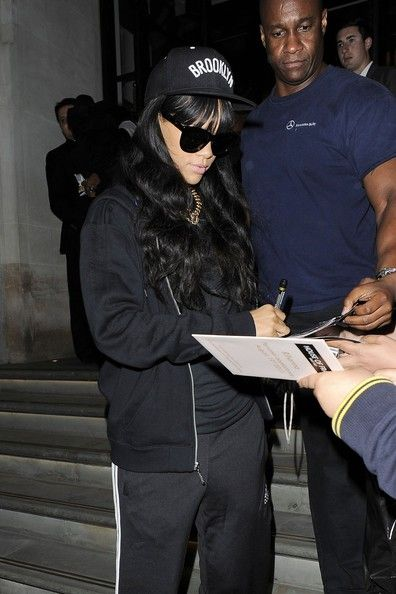 Rihanna, dressed in black, signs autographs for fans as she leaves her hotel in London, England on June 28, 2012